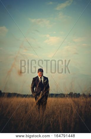 Man in black suit cross a wheat field
