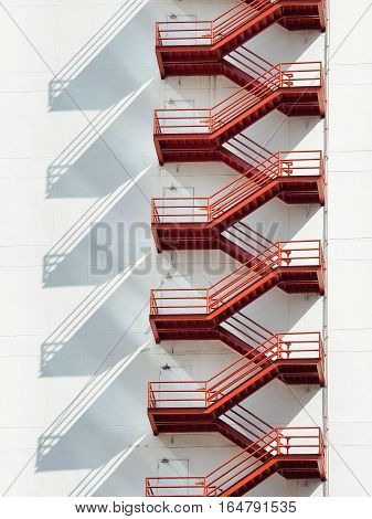 Red fire escape ladders on white building, Exterior view
