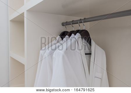 white robes with wooden hangers at dressroom