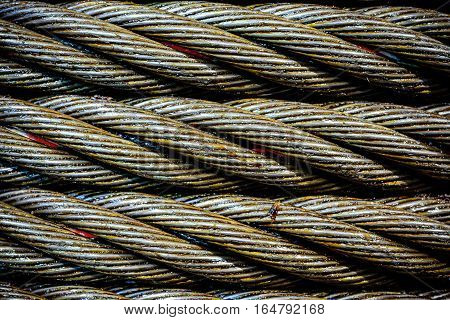 Industrial abstract background. Steel cable close-up photo. New rope lubrication.