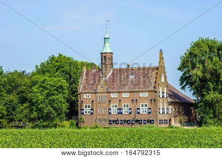 Castle-like building in a rural setting in the Netherlands. The current building was built around 1936 on the site where originally was a real castle from the 14th century. This castle was destroyed by fire and the current building contains some elements