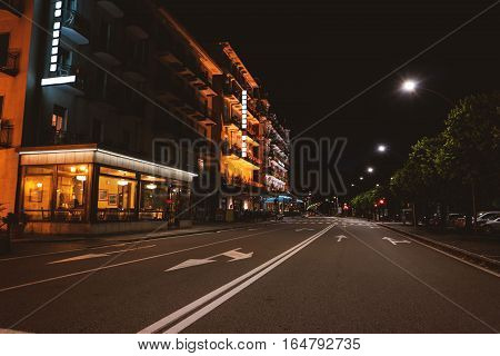 Town street at night. Buildings near the road. Hotels and restaurants.