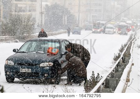 Drivers Are Trying To Install Chains On Their Tyres Under Heavy Snow Storm.