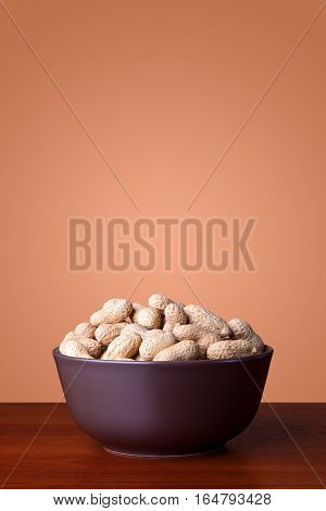 A bowl full of peanuts on a wooden table