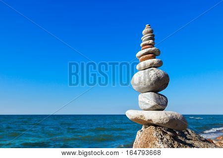 high pyramid of stones of different colors on the background of sea and blue sky