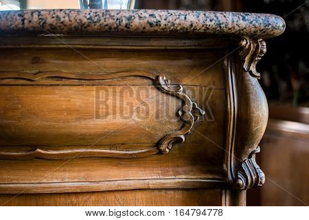 Marble top furniture. Ornament on old wooden drawer. Beauty of classic design.