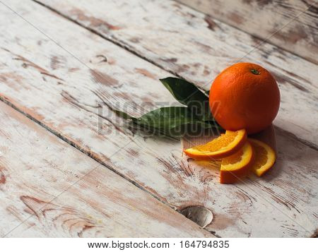 Fresh oranges fruits with green leaves on white wooden table. Text space.