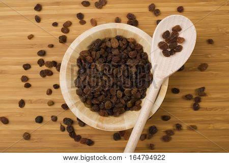Raisins in a wooden spoon on raisins background