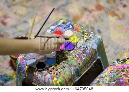 De focus child hand dips the brush in watercolor