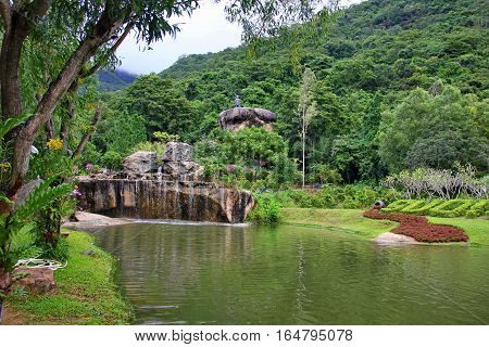 beautiful place with lots of greenery, beautiful views of the waterfall flowing over the stones, mountains covered with greenery and a pond, a figure on top of the stone