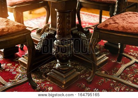 Antique wood furniture. Classic chairs on the carpet. The art of carving.