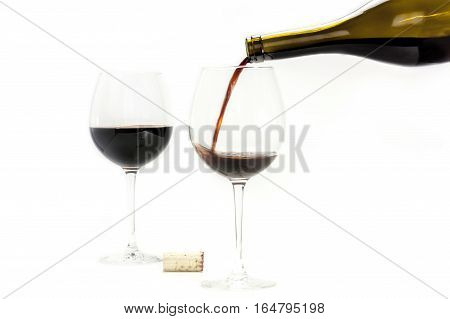 Red wine poured from a bottle into a glass, with another glass in the background, and a cork. Selective focus, white background