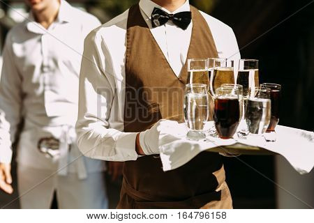Waiter Is Holding A Server With The Champagne