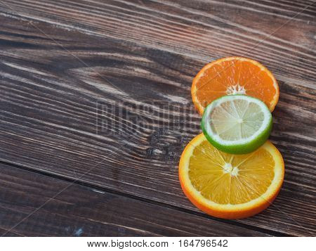 Orange, lime and tangerine slices on wooden table.