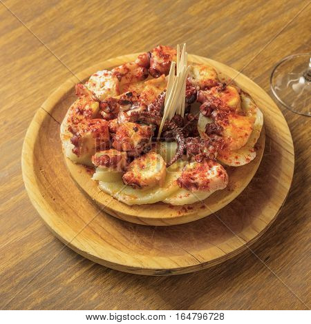 A photo of an octopus with fried potatoes, typical Spanish dish, on a traditional wooden plate, with copyspace