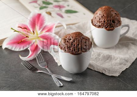 Chocolate cupcake in ceramic cup and flower
