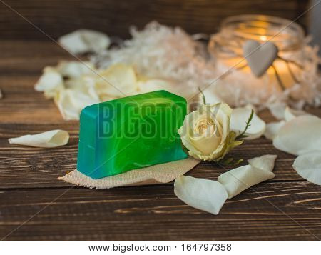 Natural handmade soap with mint, kiwi, lemongrass, lime on rustic wooden background.