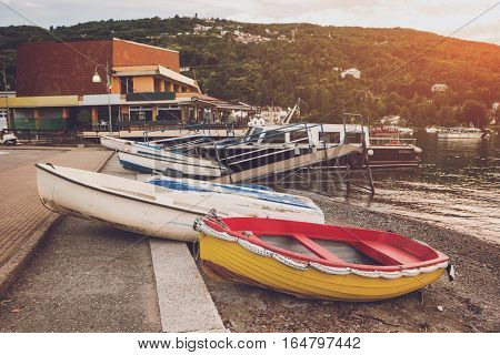 Boats on the shore. Buildings and trees on hill. Spend vacation in quiet town.