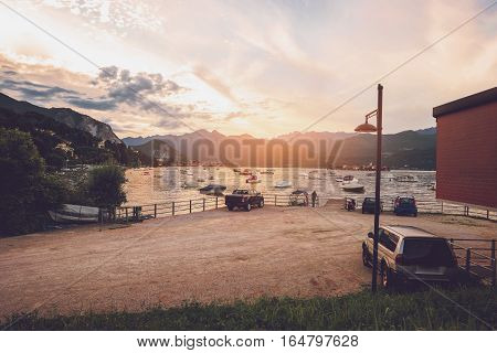 Boats, water and mountains. Landscape at sunset. Admire beauty and find inspiration.