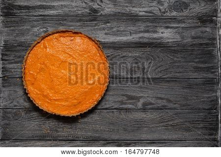 Overhead shot of freshly baked pumpkin pie on background of rustic grey wood planks. Copy space. Homemade pie cooking in fall harvest Thanksgiving autumn. Healthy food.