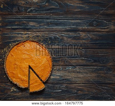 Overhead shot of freshly baked pumpkin pie on background of rustic brown wood planks. Crumbs around sliced dessert. Copy space. Homemade pie cooking in fall harvest Thanksgiving autumn. Healthy food.