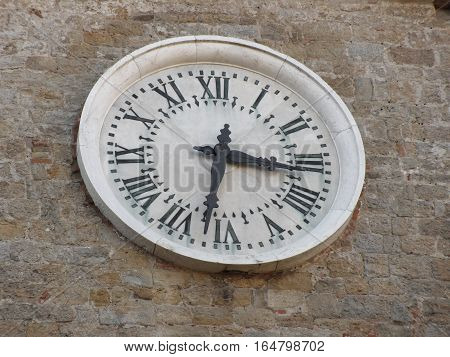 The clock on the facade of the Palazzo dei Priori in Volterra village province of Pisa . Tuscany Italy