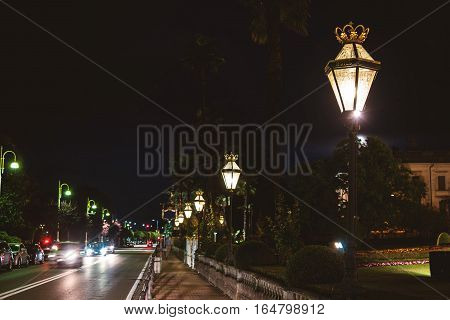 Cars in town at night. Street lamps and park. Discover the beauty of Stresa.