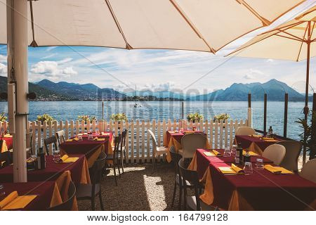 Tables and chairs near water. Mountains at distance. Restaurant in the open air.