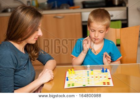 young boy plays ludo game with his mother on a table in living room