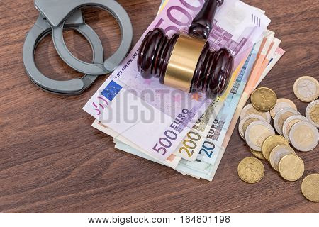 handcuffs with law hammer and euro bills coin on desk. business concept.
