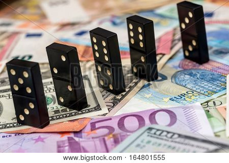 dominoes on different euro and dollar banknotes.