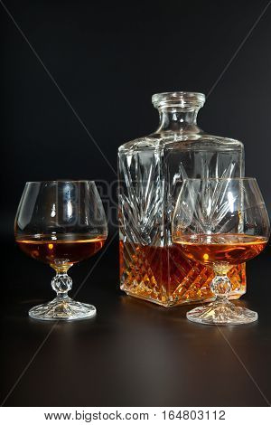 Glass of brandy and a carafe on a dark background