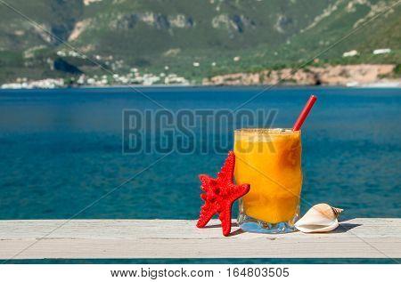 Glass of fresh orange juice next to shells on the seaside background. Fresh orange juice, seaside and seashells. Horizontal. Daylight.