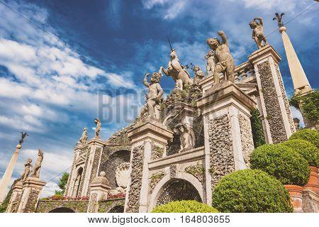 Statues of children. Sculptures, plants and sky. Visit garden of Isola Bella.