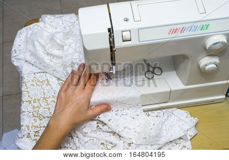 Woman's hands working on sewing machine. Black and white. seamstress sewing a white cloth