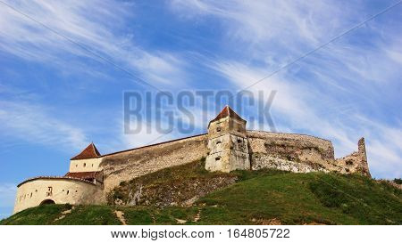 on a rocky green hill peasant fortified castle with ramparts with two towers under azure skies
