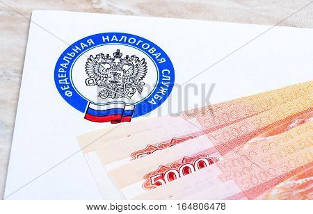 MOSCOW RUSSIA - JANUARY 9 2017: Tax payment notice letter with logo of the Federal Tax Service of Russia and ruble banknotes above. Tax payment concept