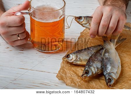 Male Hand With A Glass Of Beer And Dry Fish On A White Table. Traditional Russian Appetizer