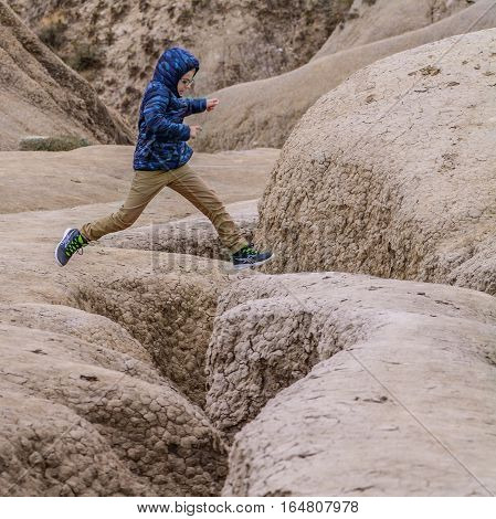 Boy jumping over dried ground covered with cracks. Boy jumping over dry land in natural park with muddy volcanoes dramatic landscape.