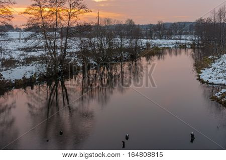 Pictorial evening landscape with Hrun' river at winter sunset time Poltavskaya oblast Ukraine