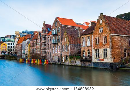 Gent (Ghent) - February 2016, Belgium: Old medieval brick houses in traditional style and water canal in one of the most popular tourist destination of Belgium