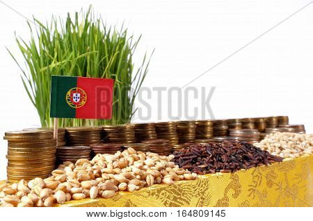 Portugal Flag Waving With Stack Of Money Coins And Piles Of Wheat And Rice Seeds
