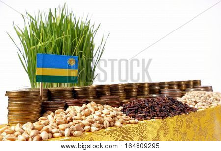 Rwanda Flag Waving With Stack Of Money Coins And Piles Of Wheat And Rice Seeds