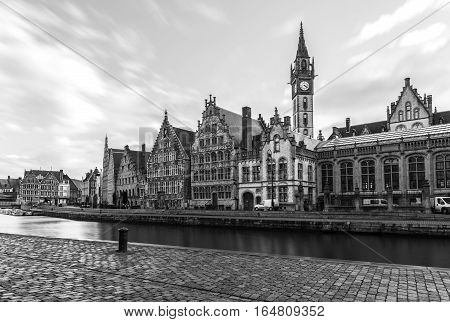 Historic buildings, old clock tower and water canal in medieval Belgian city of Gent (Ghent is a port city in northwest Belgium), popular tourist destination in Europe, black and white photography