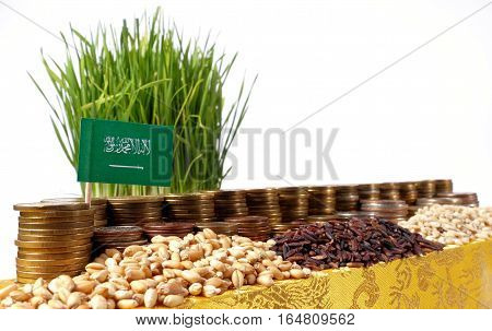 Saudi Arabia Flag Waving With Stack Of Money Coins And Piles Of Wheat And Rice Seeds