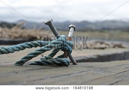 Rustic makeshift mooring bollard with blue rope snow capped mountains in the background