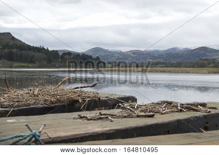 Snowdonia, Snow capped mountains, behind a tranquil river view with wooden jetty with sticks and twigs landscape