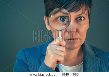 Beautiful business woman with magnifying glass - search discover explore investigate and analyze concept.