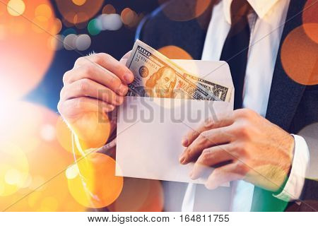 Bribery and corruption concept in business and politics with caucasian businessman taking cash money from envelope on city street at night