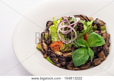 Warm salad with veal on a white plate. Vegetables herbs